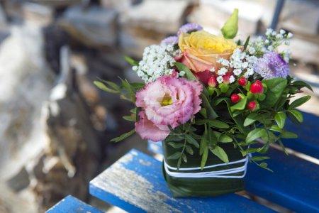 Photo pour Bel arrangement floral sur une chaise en bois bleu - image libre de droit
