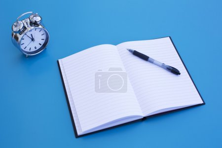 Photo for Alarm clock on blue table with notepad and pen - Royalty Free Image