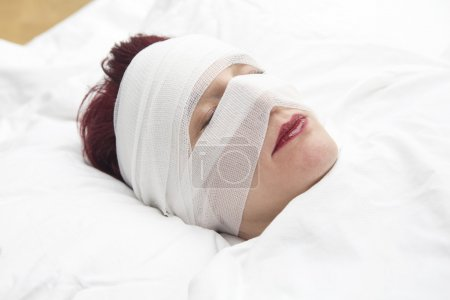 closeup of woman in bed with bandages wrapped around her head