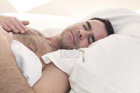 shirtless man sleeping in bed