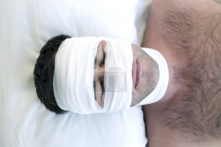 man in bed with bandages
