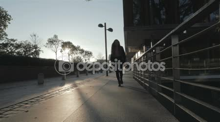 Silhouette of young girl walking joyfully in the city streets, slow motion.