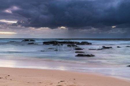 Photo for Clouds and rainy day beach sunrise at Bateau Bay on the Central Coast, NSW, Australia. - Royalty Free Image