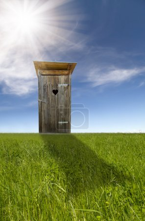 Wooden toilet, green field, blue sky
