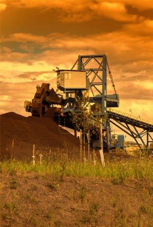Photo pour Une pelle à roue géante dans une mine de charbon au coucher du soleil, lieu industriel - image libre de droit