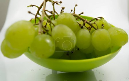 Photo for Fresh green grapes in a bowl isolated on pink background. Selective focus on the fresh green grapes. - Royalty Free Image
