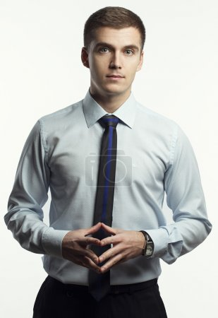 portrait of young man in a classic shirt and tie with blue line posing on a white  background. Concept of good  businessman