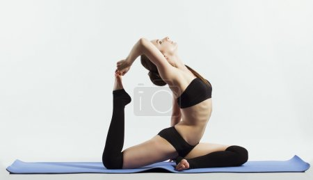 young woman doing yoga (sports exercises). isolated on white. the concept of a healthy lifestyle