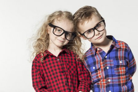 Funny lovely children.  fashionable little boy and girl in glasses, jeans, white t-shirts and plaid shirts.stylish kids in casual shoes. fashion children