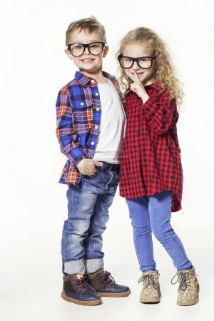 Funny lovely children.  fashionable little boy and girl in glasses, jeans, white t-shirts and plaid shirts. stylish kids in casual clothes in shocked. fashion children