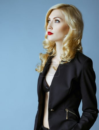 Young blond sexy woman in a business suit on a grey background.