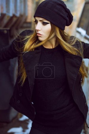 Emotive portrait of beautiful woman model with long curly hair  and with dark evening make-up, wearing black  jacket.
