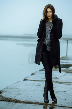 High fashion concept. Emotive portrait of beautiful brunette with long curly hair and perfect make up wearing black coat. Windy and misty weather.