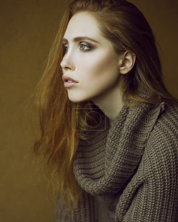 Studio shot. Emotive portrait of fashionable model with long curly red hair and natural make-up posing over wooden background. Perfect skin and green eyes. Urban style.