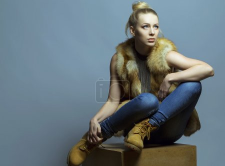 Emotional portrait of a gorgeous fashion blond model in blue jeans and casual waistcoat posing over blue background.  Studio shot. Hipster style. Copy space