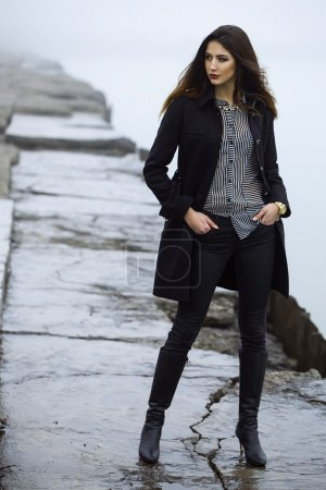 High fashion concept. Emotive portrait of beautiful brunette with long curly hair and perfect make up wearing black coat. Windy and misty weather. Italian luxurious style. Outdoor shot