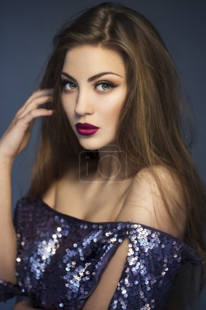 Sexy Beauty Girl with purple-red Lips. Provocative Make up. Luxury Woman with Green Eyes. Fashion Brunette Portrait wearing in dress with sparkles. Gorgeous Woman Face. Long Hair