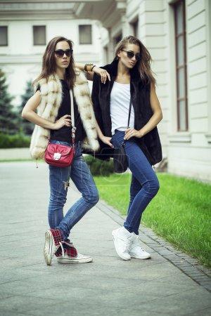 Photo pour Prise de vue de mode de deux belles filles élégantes dans le coucher du soleil portant des lunettes de soleil, gilets de fourrure. Deux jeunes femmes en plein air dans la rue. Shopping inspiration - image libre de droit