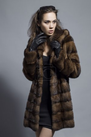 Photo for Sexy Beauty Girl with natural  Make up.  Fashion Brunette  Portrait of a girl dressed in fur coat,  black dress and sunglasses posing on a grey background. Retro style - Royalty Free Image