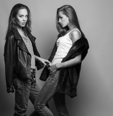 Fashion shot of two elegant beautiful girls (brunette and blonde) in studio on grey background, dressed in casual clothes . Shopping inspiration. Monochrome (black and white)  photo