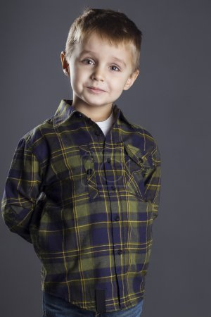 Funny child. fashionable little boy in  jeans, white shirt and plaid shirt. stylish kid  in shock and surprise. fashion children
