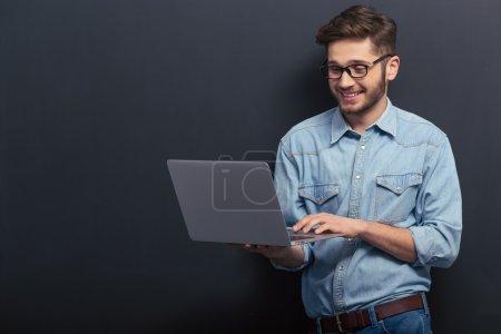 Photo pour Beau jeune étudiant en jeans chemise et lunettes utilise un ordinateur portable et souriant, debout contre tableau noir - image libre de droit