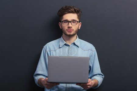 Photo for Handsome young student in jeans shirt and eyeglasses is holding a laptop and looking at camera, standing against blackboard - Royalty Free Image