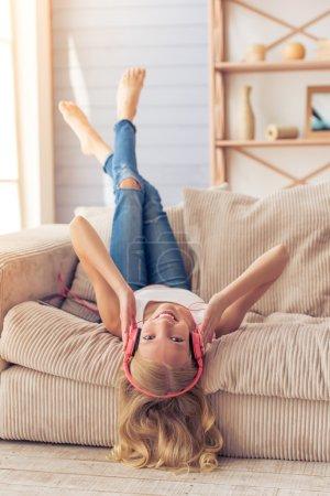 Photo pour Jolie adolescente blonde dans un casque écoute de la musique, regarde la caméra et sourit tout en étant couchée sur le dos, les jambes en l'air, sur le canapé à la maison - image libre de droit