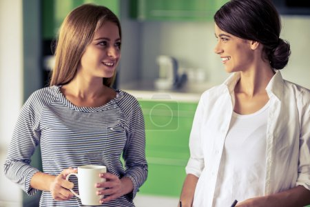 Photo for Two beautiful girls are talking, looking at each other and smiling while standing in the kitchen at home. One girl is holding a cup - Royalty Free Image