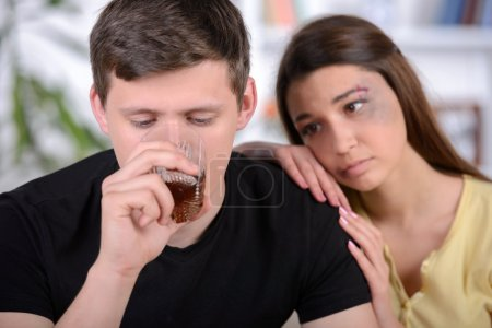 Photo for Scared woman is looking on drunk man on foreground. Having bruises on her pretty face - Royalty Free Image