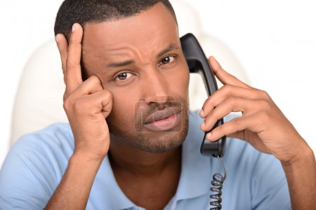 Foto de Empresario en el trabajo. Joven empresario africano confiado hablando por teléfono y usando la computadora mientras está sentado en su lugar de trabajo - Imagen libre de derechos
