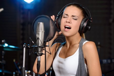 Portrait of young woman recording a song in a prof...
