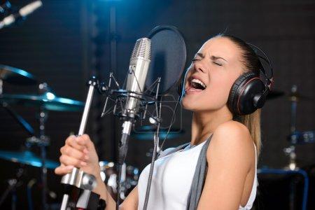 Photo pour Portrait de jeune femme enregistrant une chanson dans un studio professionnel - image libre de droit