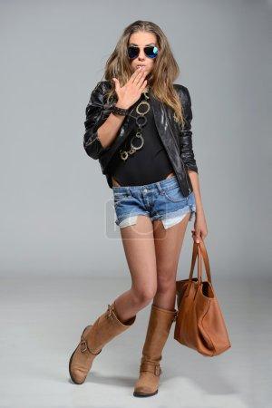 Photo pour Rock style belle jeune femme dans des lunettes sur fond gris - image libre de droit