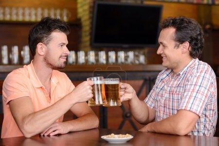 Foto de Amigos en el pub de cerveza. Dos alegres amigos bebiendo cerveza y hablando en el bar - Imagen libre de derechos
