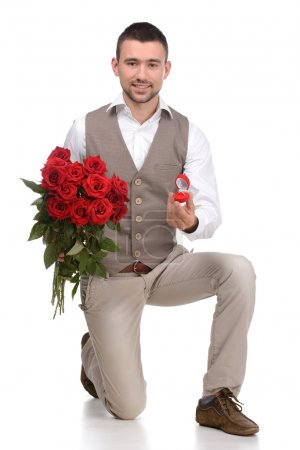 Photo pour Will you marry me? Young man in full suit standing on one knee and making a proposal while isolated on white background - image libre de droit