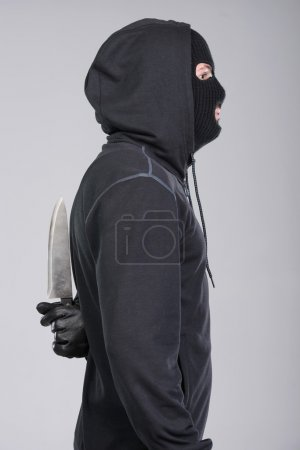Photo for Masked man aims with knife. on gray background - Royalty Free Image
