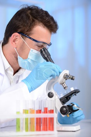 Photo pour Clinicien sérieux étudiant un élément chimique en laboratoire avec un microscope - image libre de droit