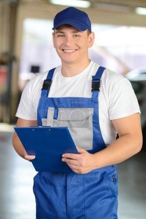Photo pour Service de réparation automobile. Portrait d'un beau mécanicien souriant - image libre de droit