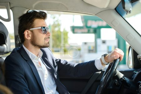 Photo pour L'homme dans sa voiture s'arrête à la station-service - image libre de droit