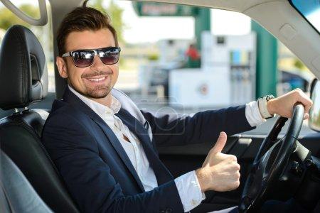 Photo pour L'homme dans sa voiture s'arrête à la station d'essence - image libre de droit
