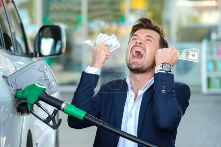 Emotional businessman counting money with gasoline...