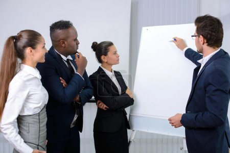 Photo pour Young multiethnic business team planning a new strategy standing grouped in front of a flip chart analyzing a chart - image libre de droit