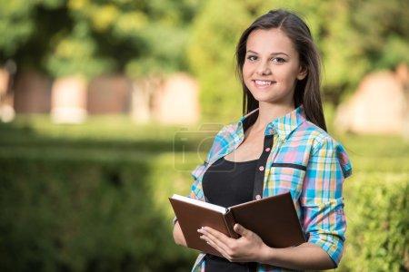 Photo pour Portrait d'un jeune étudiant magnifique avec bâtiment universitaire en arrière-plan . - image libre de droit