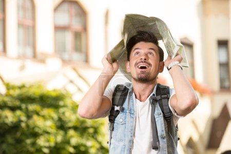 Photo pour Joyeux jeune homme, touristes dans la ville avec carte touristique . - image libre de droit