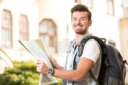 Photo for Trendy young man in the town with touristic map and backpack. - Royalty Free Image