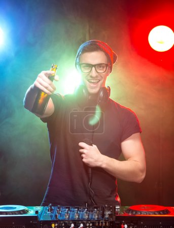 Foto de Portrait of a young dj with mixer, on foggy background. - Imagen libre de derechos