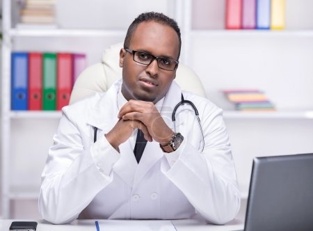 Photo for Portrait of young African American doctor is sitting in his office and looking at the camera. - Royalty Free Image