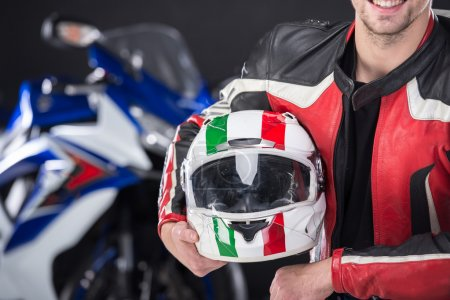 Photo pour Portrait d'homme souriant avec casque. La moto est sur fond noir . - image libre de droit