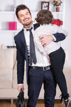 Photo for Little son meets his businessman father from work. - Royalty Free Image